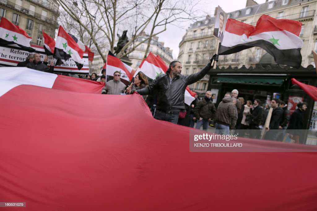 People wave Syrian flags as they take part in a demonstration in support of Syria's president on February 2, 2013 in Paris. AFP PHOTO KENZO TRIBOUILLARD