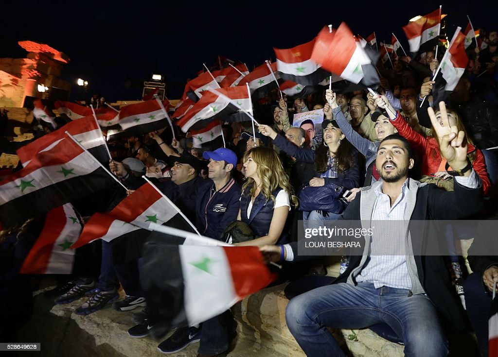 People wave Syrian national flags as they attend a music concert in the ancient theatre of Syria's ravaged Palmyra on May 6, 2016 following its recapture by regime forces from the Islamic State group fighter. Syrian troops backed by Russian air strikes and special forces on the ground recaptured UNESCO world heritage site Palmyra from Islamic State (IS) group fighters in March 2016. BESHARA