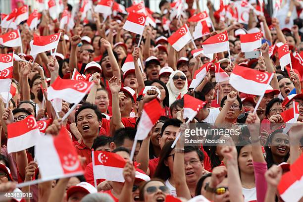 People wave the flags during the National Day Parade at Padang on August 9 2015 in Singapore Singapore is celebrating her 50th year of independence...