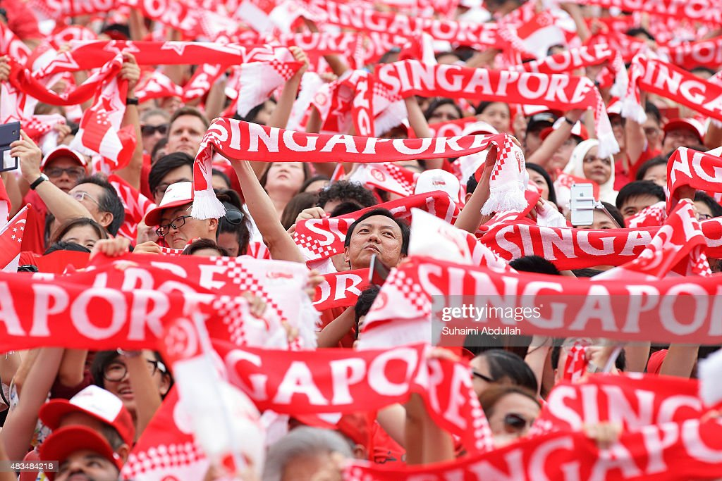 People wave the 'Singapore' scarf during the National Day Parade at Padang on August 9, 2015 in Singapore. Singapore is celebrating her 50th year of independence on August 9, 2015.
