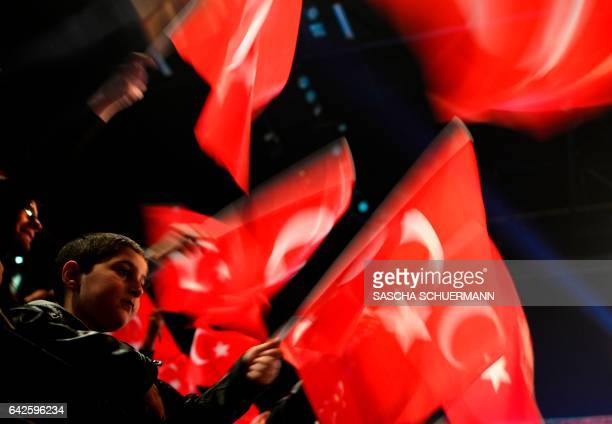 People wave Turkish flags during a campaigning event with the Turkish Prime Minister in Oberhausen western Germany on February 18 2017 Turkish Prime...