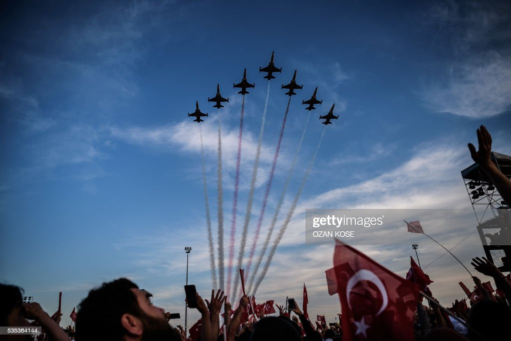 People wave Turkish national flags as Turkish Air Forces aerobatic team, Turkish stars perform during a rally to mark the 563rd anniversary of the conquest of Istanbul by Ottoman Turks on May 29, 2016 in Istanbul. / AFP / OZAN