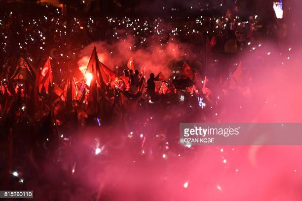 TOPSHOT People wave Turkish national flags as Turkish President adresses a speech on July 15 2017 during the first anniversary of failed coup in...