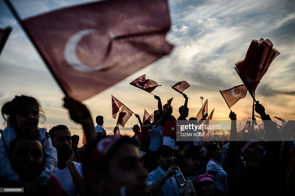 People wave Turkish national flags as Turkish President speaks during a rally to mark the 563rd anniversary of the conquest of Istanbul by Ottoman Turks on May 29, 2016 in Istanbul. / AFP / OZAN