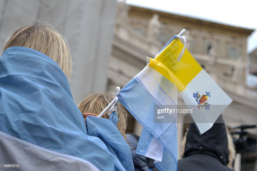 People waves Argentinian and Vatican flags during the pope's first Angelus prayer at St Peter's square on March 17, 2013 at the Vatican. Pope Francis begins his papacy in earnest today ahead of his formal inauguration mass, with a weekly prayer address used by previous pontiffs to comment on international affairs. The pope's first Angelus prayer, delivered from a window high above St Peter's Square, is a chance for the first Latin American pontiff to begin to sketch out a more global vision for the role of the Roman Catholic Church.