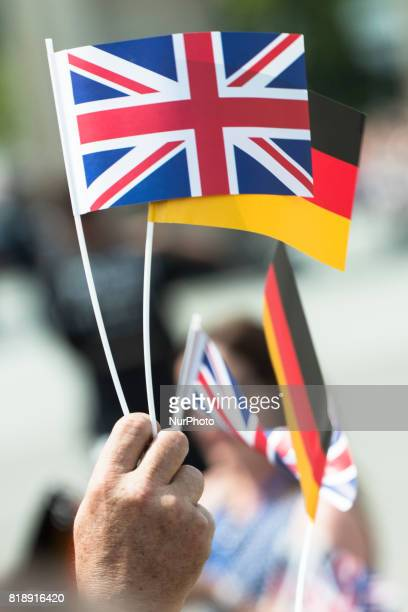 People waves British and German flags during the visit of Britain's Prince William Duke of Cambridge and his wife Kate the Duchess of Cambridge at...