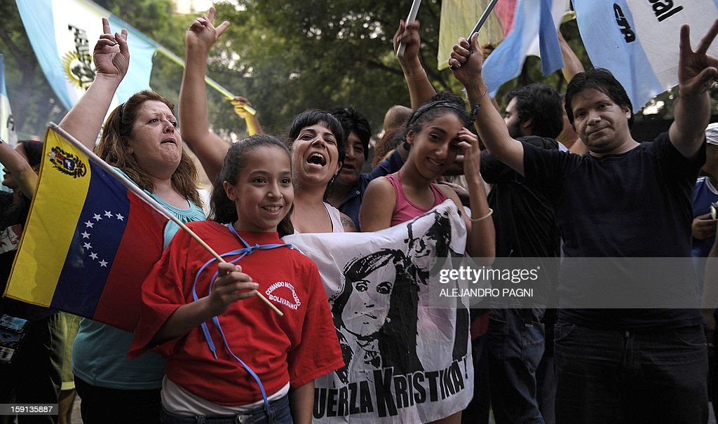 People waves flags, gesture and chant slogans in support of Venezuelan President Hugo Chavez´s recovery in front of the Venezuelan embassy in Buenos Aires on January 8, 2013. The President of the National Assembly Diosdado Cabello announced today that due to health reasons, Chavez will not be able to take the oath to be sworn in for a fourth term in office next January 10. A constitutional fight intensified with the government planning a massive show of support in the streets on the day he is supposed to be sworn in. Chavez, who underwent his fourth round of cancer surgery in Havana nearly a month ago, is suffering from a severe pulmonary infection that has resulted in a respiratory insufficiency. The sign reads 'Long live Commander Chavez. Long live Nestor (Kirchner), Strength Cristina (Fernandez). We are overcoming'. AFP PHOTO / ALEJANDRO PAGNI
