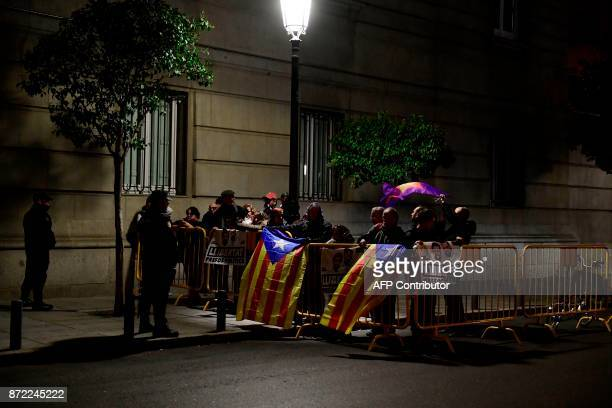 People waving Catalan proindependence Estelada flags hold a poster reading 'Freedom to political prisoners' with pictures of detained leaders of...