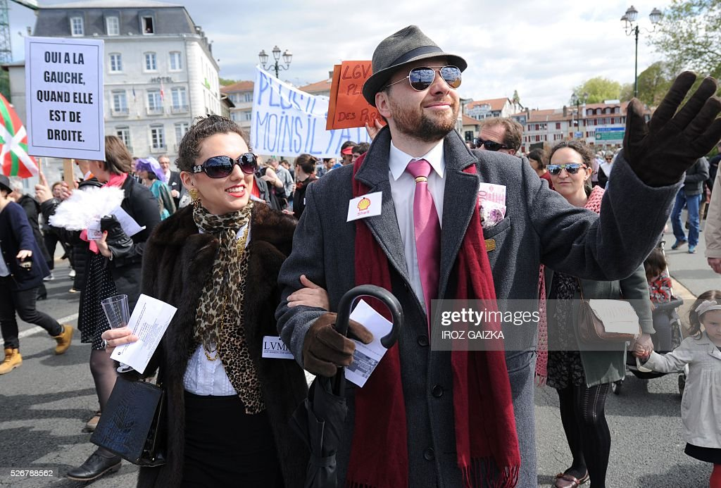 People wear badges of French luxury group LVMH and Anglo-Dutch oil company Shell as members of the movement 'Bizi !' ('live' in Basque) stage a 'Rich peoples protest' to mark May Day in Bayonne on May 1, 2016. / AFP / IROZ