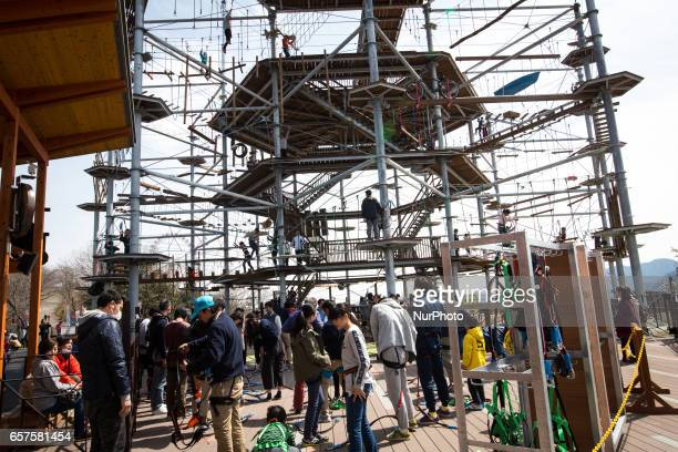 People wear body harness as they prepare to try on the newly open athletic climbing attraction in Sagamiko Resort Pleasure Forest in Kanagawa...