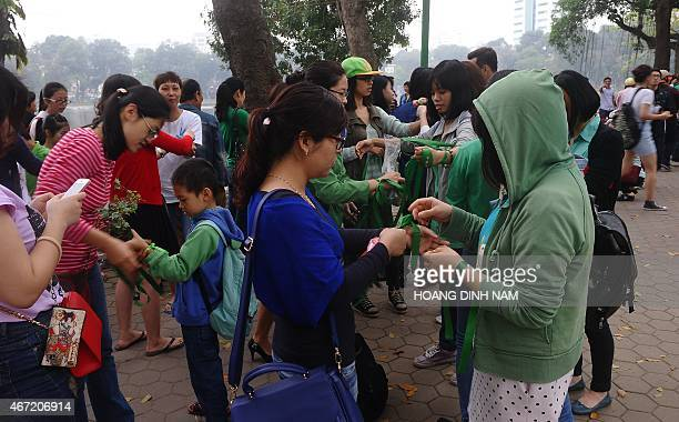 People wear green ribbons as they join a rally protesting against a treefelling plan by the municipal authorities in Hanoi on March 22 2015 Vietnam...