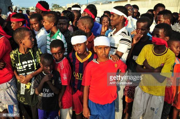 People wear headbands as a sign of anger as they protest against the deadly bomb attack in Mogadishu on October 15 after a truck bomb exploded...