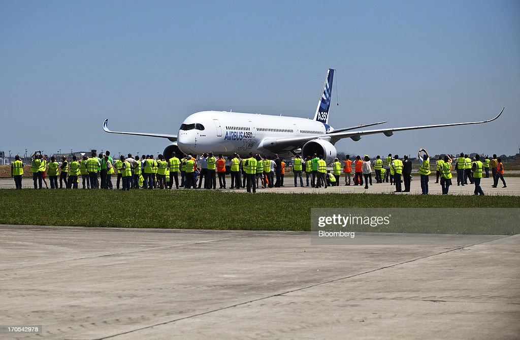 People wear high visibility jackets as they stand on the runway in front of an Airbus SAS A350, produced by a unit of European Aeronautic, Defence & Space Co. (EADS), following its first flight in Toulouse, France, on Friday, June 14, 2013. Airbus SAS's new A350 wide-body returned from its maiden flight after a four-hour airborne test of the long-range airliner, in a show of confidence that the jet can enter service in late 2014 and challenge Boeing Co. Photographer: Balint Porneczi/Bloomberg via Getty Images