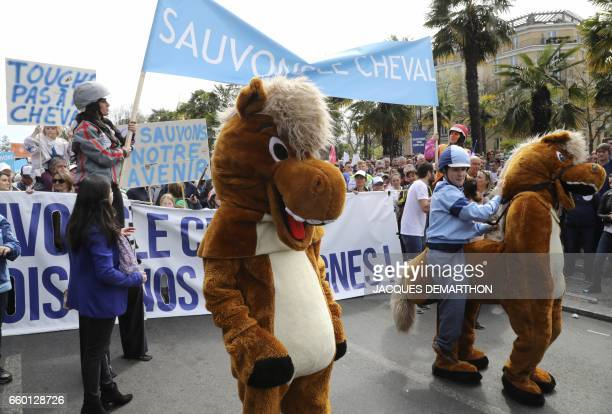 People wear horse and jockey costumes as other hold a banner which translates as 'Save horse' during a demonstration of equestarian professionals to...