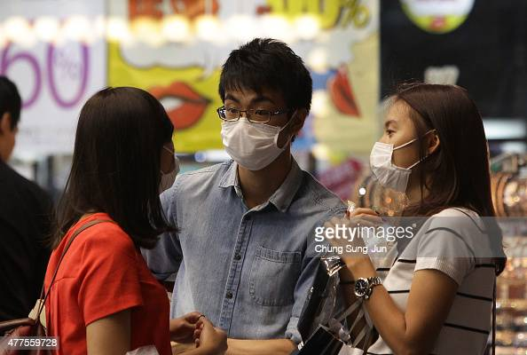 People wear masks as a precaution to protect them against the MERS virus in downtown Seoul on June 18 2015 South Korea WHO announced it does not...