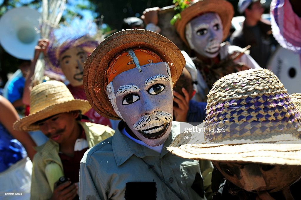 People wear masks during the 'Torovenado' carnival in the framework of the celebrations honouring Saint Jerome, the patron saint of Masaya, 30 km from Managua, on November 18, 2012. The festivities honouring Saint Jerome - the longest festivities in Nicaragua - began on September 20 and will end the last Sunday of November. AFP PHOTO/Hector RETAMAL