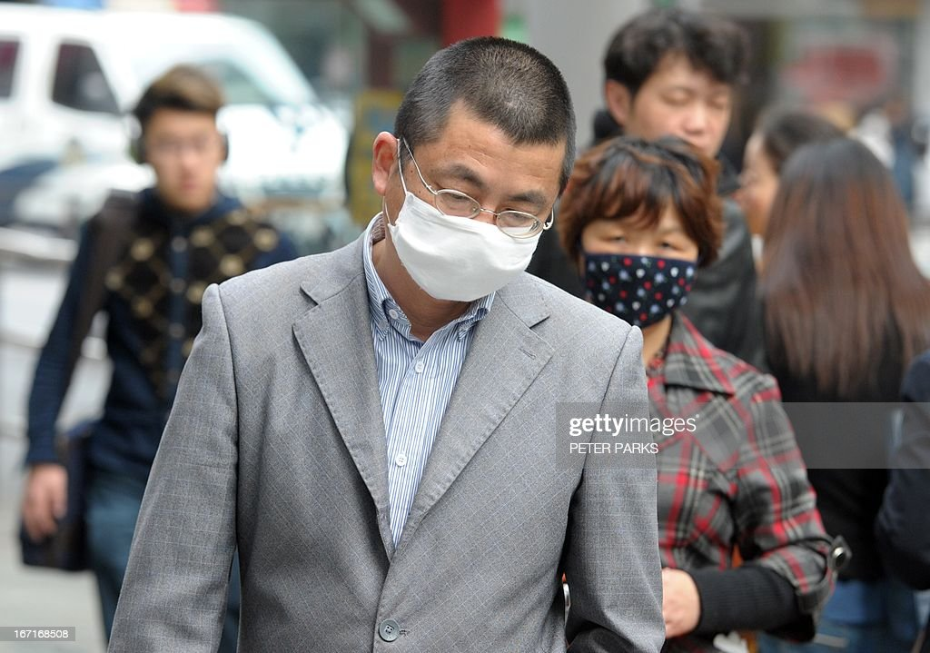 People wear masks on a street as a WHO team wrapped up a visit to Shanghai, centre of China's bird flu outbreak on April 22, 2013. Keiji Fukuda, Assistant Director-General for Health Security and Environment in the World Health Organisation (WHO) reitered at a press conference that there is still no evidence a new strain of deadly bird flu is passing in a 'sustained' fashion from person to person, amid worries some families may have infected each other. AFP PHOTO/Peter PARKS