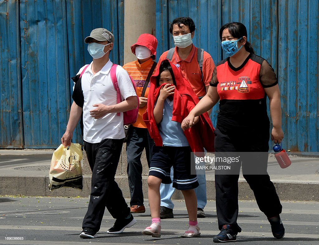 People wear masks to protect against air pollution and dust in Beijing on May 19, 2013. China will more than double the number of cities covered by air quality monitoring, as part of efforts to tackle heavy smog that has sparked huge public anger. Swathes of acrid haze have repeatedly shrouded large parts of the country in recent months, provoking outrage among Internet users and unusual outspoken calls for action, in the state-run media. AFP PHOTO / Mark RALSTON