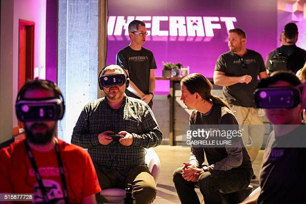 People wear Oculus goggles as they test out the Minecraft for Gear VR at a press demonstration at The Village event space in San Francisco California...