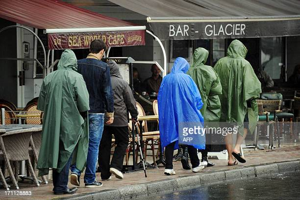 People wear ponchos as they walk under the rain past nearly empty terraces in the western French coastal city of La Rochelle on June 22 2013 AFP...