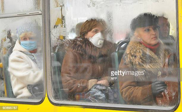 People wear protective masks as they ride a bus in the western Ukrainian city of Lviv on November 4 2009 The World Health Organisation said today...