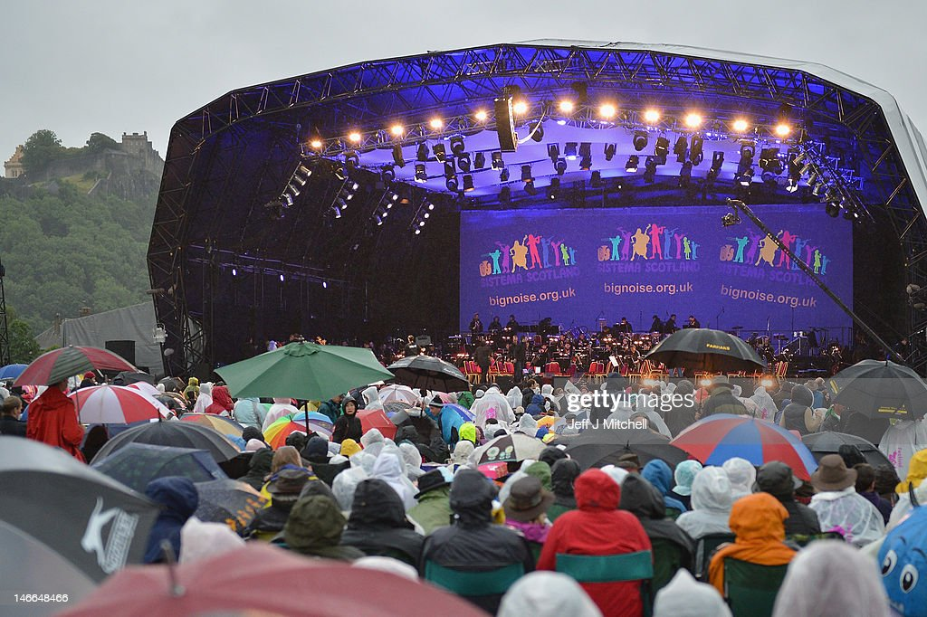 People wear rain garments while watching Maestro Gustavo Dudamel conduct the children from the Big Noise Orchestra during the Big Concert on June 21, 2012 in Stirling, Scotland. The Big Concert is the opening event of the London 2012 festival. The special outdoor event set against the backdrop of Stirling Castle, features a full performance by lead by conductor Gustavo Dudamel and the Simon Bolivar Orchestra of Venezuela.