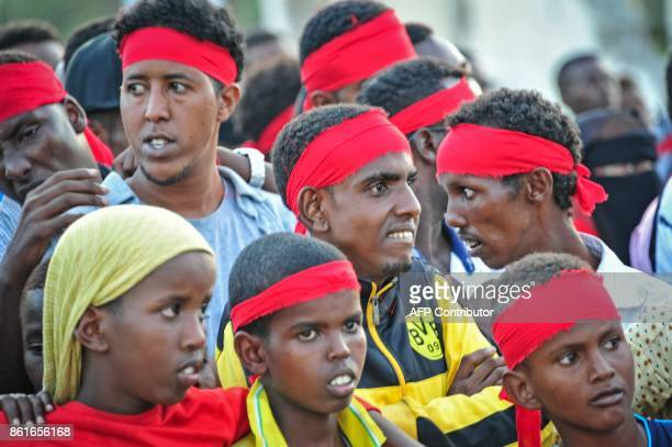 People wear red headbands as a sign of anger as they protest against the deadly bomb attack in Mogadishu on October 15 after a truck bomb exploded...
