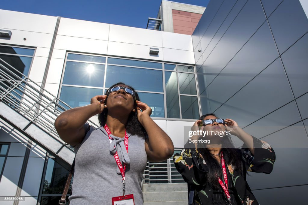 People wear solar viewing glasses while looking at the sun during a solar eclipse at the California Independent System Operator (ISO) headquarters in Folsom, California, U.S., on Monday, Aug. 21, 2017. Millions of Americans across a 70-mile-wide (113-kilometer) corridor from Oregon to South Carolina will see the sky darken as the sun disappears from view total during the eclipse. Photographer: David Paul Morris/Bloomberg via Getty Images