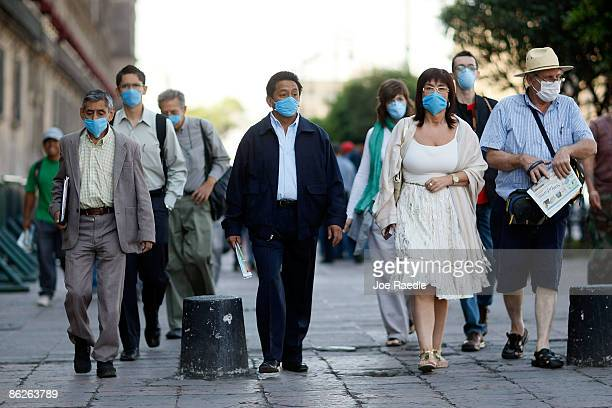 People wear surgical masks to help prevent being infected with the swine flu as they walk through the street on April 28 2009 in Mexico City Mexico...