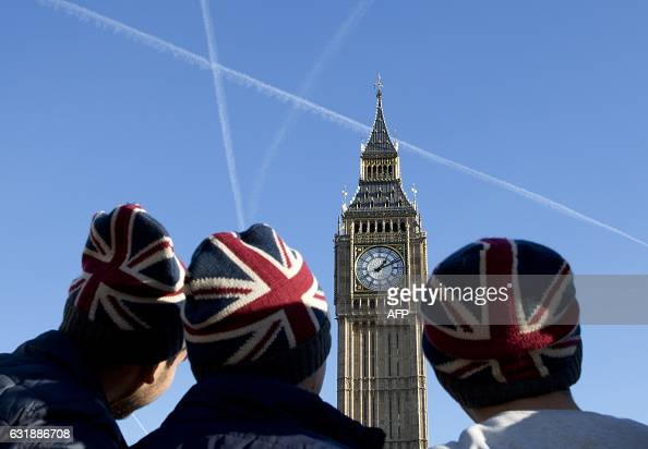 TOPSHOT People wear Union flagthemed hats as they look at the Elizabeth Tower better known as 'Big Ben' near the Houses of Parliament in London on...