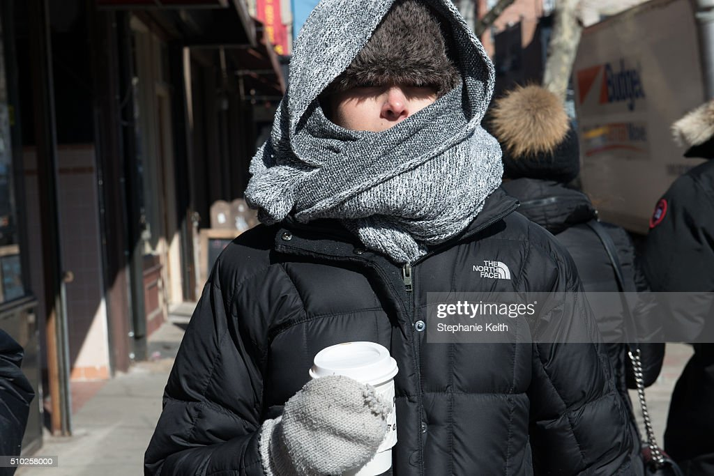 People wear warm winter clothes during an arctic chill that brought frigid temperatures on February 14, 2016 in the Brooklyn borough of New York City. The city broke a 100-year record February 14, as emputures dropped minus 1 degree Fahrenheit.