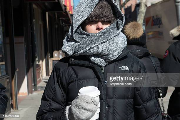 People wear warm winter clothes during an arctic chill that brought frigid temperatures on February 14 2016 in the Brooklyn borough of New York City...