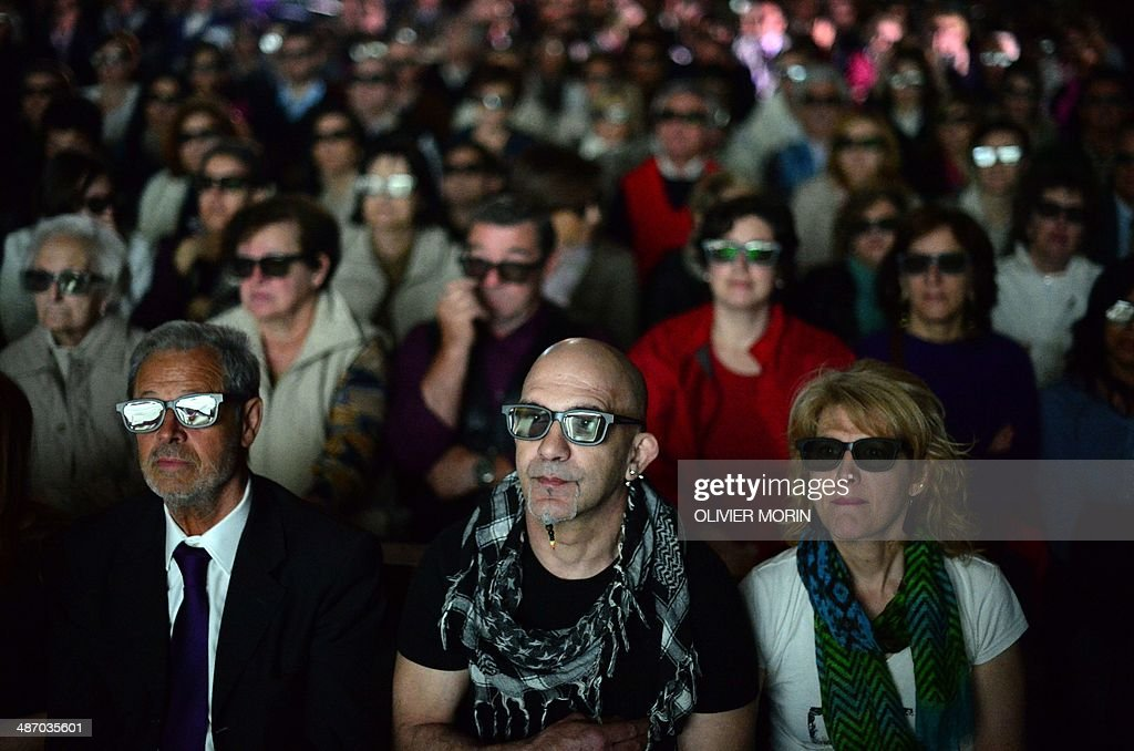 People wearing 3D glasses follow in the church of Sotto il Monte Giovanni XXIII in Milan the 3D broadcast of the canonisation mass of Popes John...