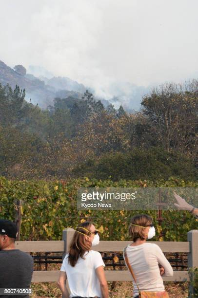 People wearing a mask look at smokes coming from a wildfire beyond a vineyard in Sonoma County California on Oct 12 2017 Wildfires in Northern...