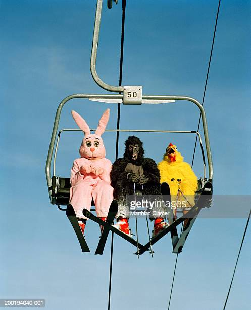 People wearing animal costumes riding ski lift