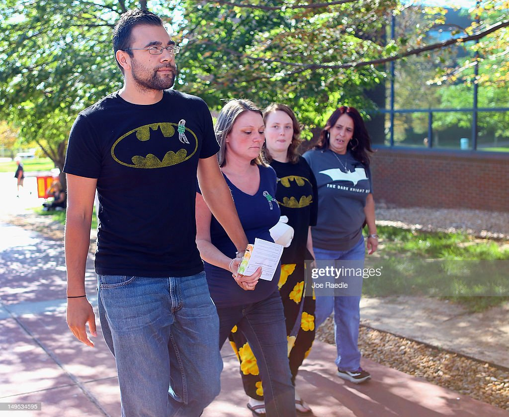 People wearing Batman shirts arrive at the Arapahoe County Courthouse for suspect James Holmes' arraignment hearing July 30, 2012 in Centennial, Colorado. James Holmes, 24, who is accused of killing 12 people and injuring 58 in a shooting spree July 20, during a screening of 'The Dark Knight Rises.' in Aurora, Colorado.