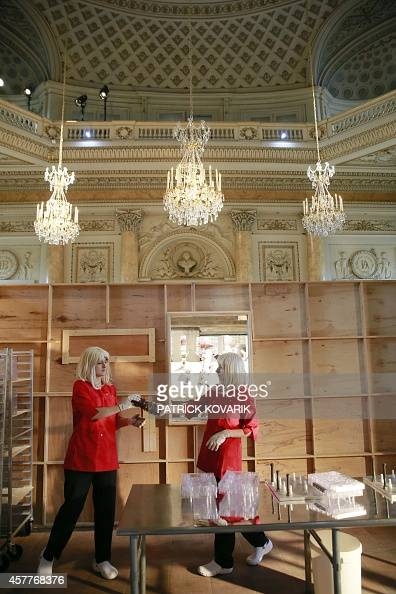 People wearing blonde wigs prepare items made with chocolate during the presentation of the - Hotel de la monnaie ...