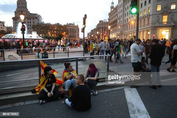 People wearing Catalan independence flags sit next at Placa Catalunya square following a demonstration for Catalan independence to demand the release...