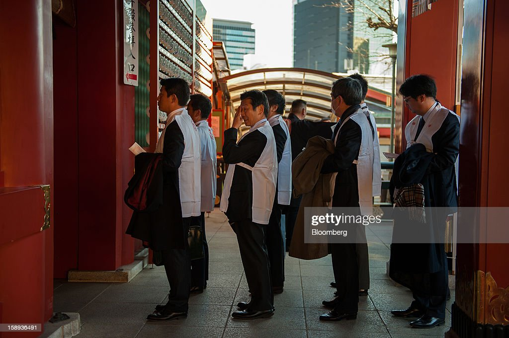 People wearing ceremonial Shinto vests wait to enter the main shrine at the Kanda Myojin shrine to offer their prayers on the first day of business in 2013 in Tokyo, Japan, on Friday, Jan. 4, 2013. Japan's deflation-plagued economy has contracted 7 percent since 2007 as six prime ministers, including Shinzo Abe in his first term, failed to reverse the course. Photographer: Noriko Hayashi/Bloomberg via Getty Images