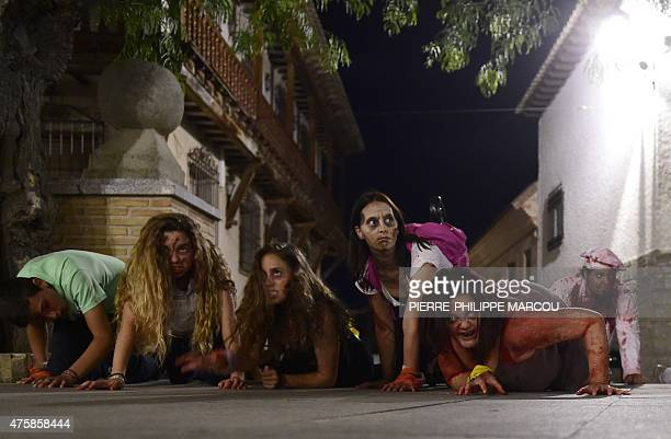 People wearing cinema style makeup to resemble the living dead crawl along a street during the role game 'Survival Zombie' in Olias del Rey on May 30...