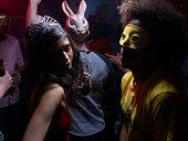 People wearing costumes, dancing in night club