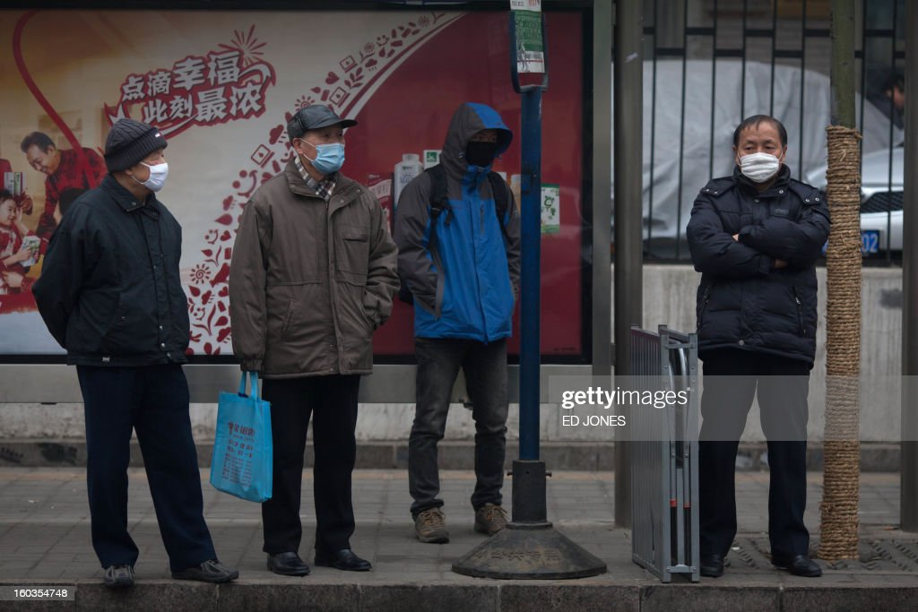 People wearing face masks stand at a bus stop during heavily polluted weather in Beijing on January 30, 2013. Residents across huge swathes of northern China battled through choking pollution at extreme levels, as Beijing was plunged into toxic twilight for the fourth time this winter. AFP PHOTO / Ed Jones