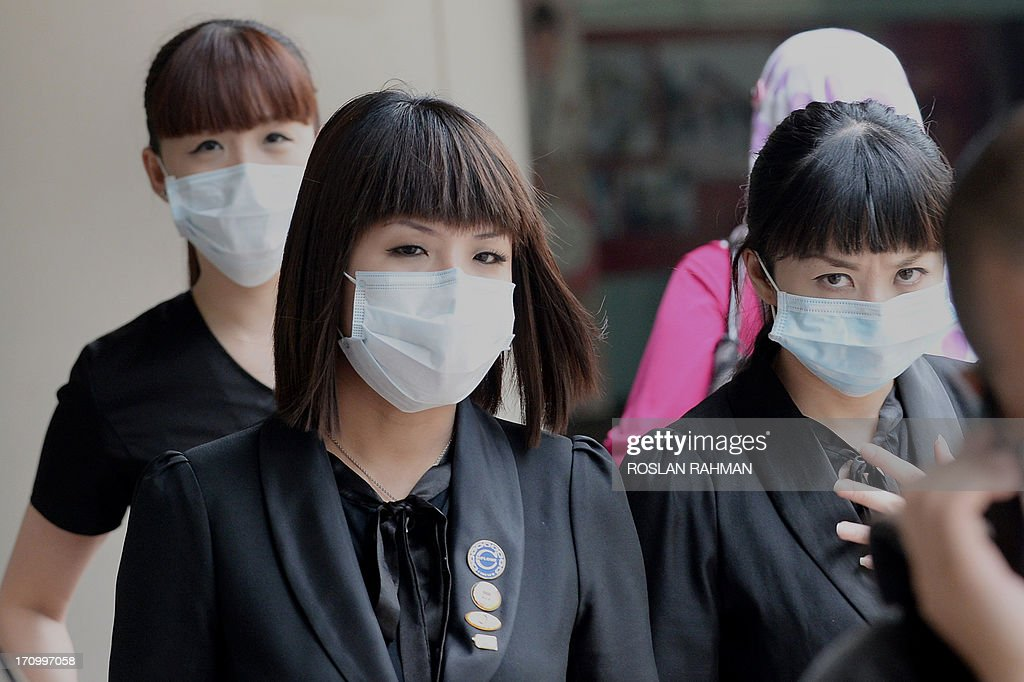 People wearing face masks walk on the street in Singapore on June 21, 2013. Singapore's smog index hit the critical 400 level on June 21, making it potentially life-threatening to the ill and elderly people, according to a government monitoring site. AFP PHOTO/Roslan Rahman