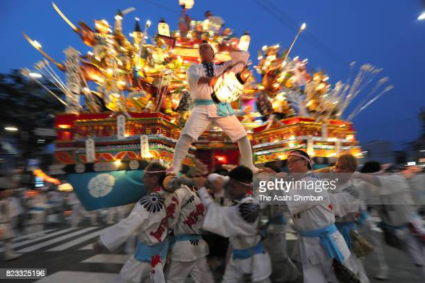 People wearing 'Happi' festival clothes swing an illuminated 'Yamagasa' float at disbandment ceremony of the Kurosaki Gion Yamagasa Festival in front...