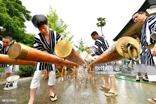 People wearing happi festival clothes wash the 'Kakibo' logs used to carry floats to purify during the 'BoArai' ritual ahead of the Hakata Gion...
