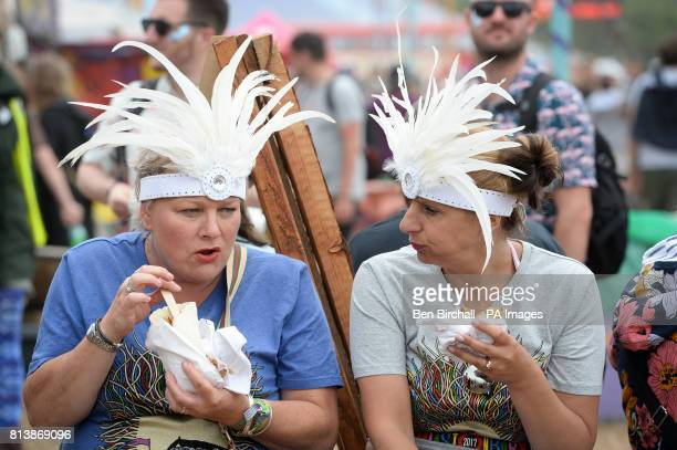 People wearing headdress eat during Glastonbury Festival Worthy Farm Somerset PRESS ASSOCIATION Photo Picture date Sunday June 2017 Photo credit...