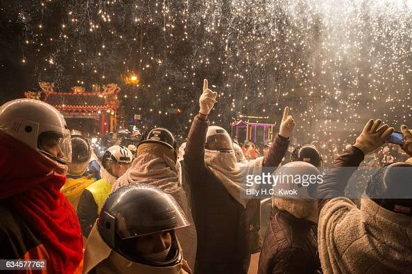 People wearing helmets get sprayed by fire sparks during the Yanshui Beehive Rockets Festival on February 10 2017 in Yanshui District Tainan City...