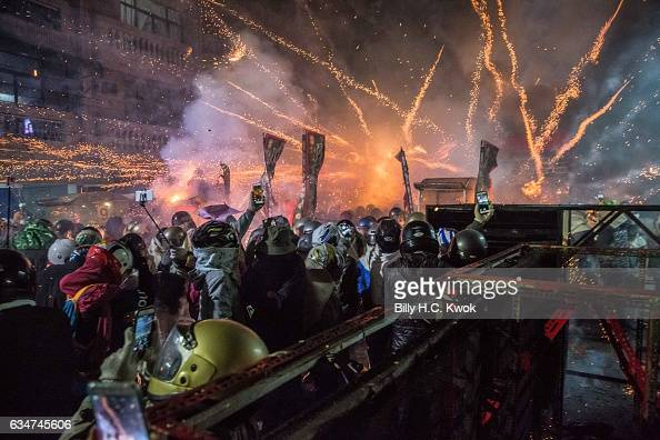 People wearing helmets get sprayed by fire sparks during the Yanshui Beehive Rockets Festival on February 11 2017 in Yanshui District Tainan City...