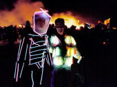 People wearing illuminated costumes walk past the burning remains of a 52foot tall wooden man September 2 2000 during the15th annual Burning Man...
