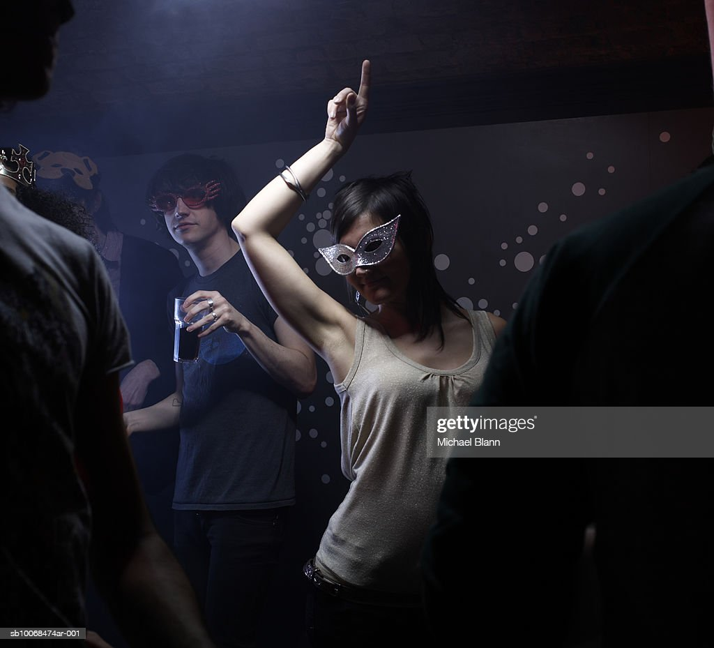People wearing masks, dancing in night club : Stock Photo